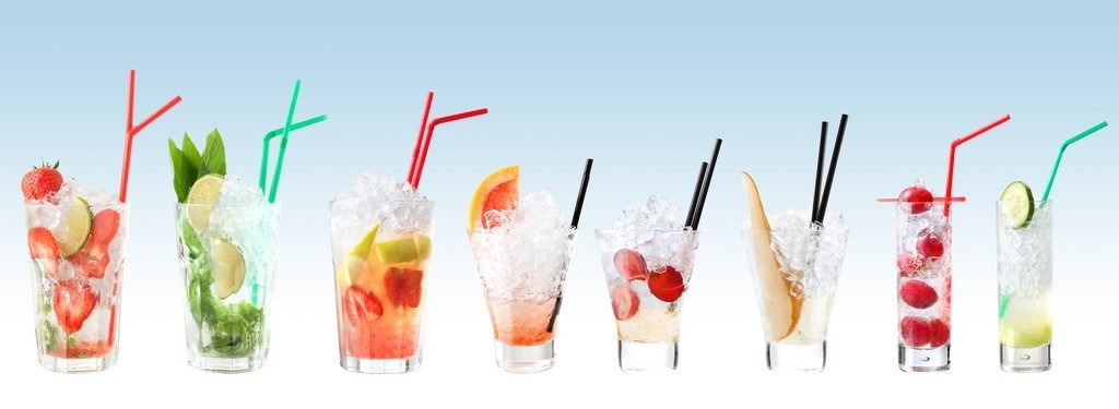 Row of colorful fruity mojito cocktails in a variety of glasses with straws.